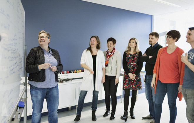 En gruppe smilende Katenga-ansatte er samlet foran en tavle. Foto.
