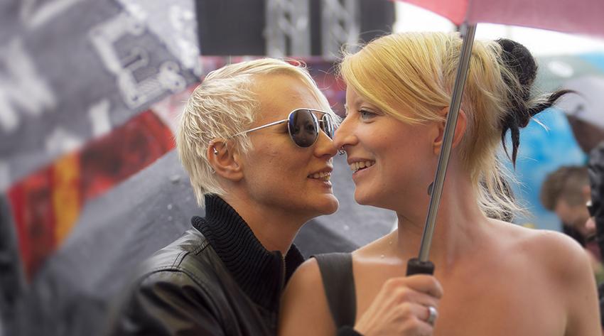 To damer smiler til hverandre under paraply. Foto.
