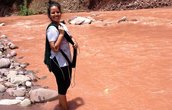Marisel Torres står smilende i ei elv, men vann til anklene. Foto.