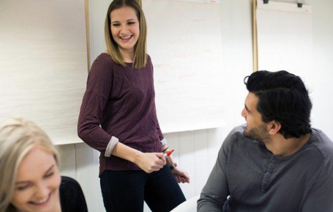 Smilende studenter i studiesituasjon. Foto.