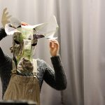 Student putting on a moose head made of paper. Photo.
