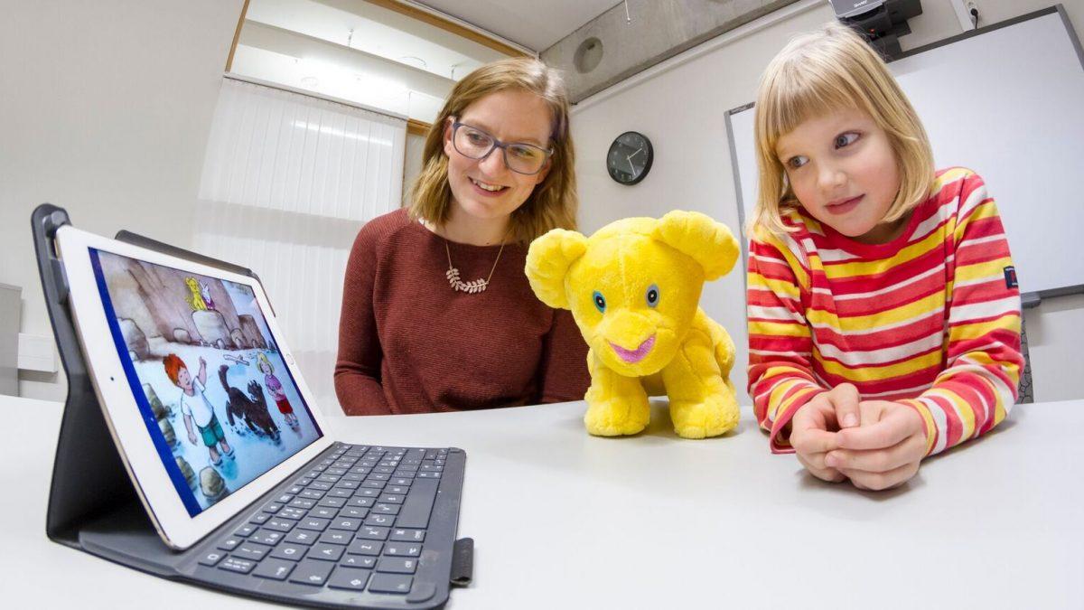 Språktest på ipad med forsker Tina Louise Ringstad og jente ca 5. år, kosedyret løveungen sitter i midten.