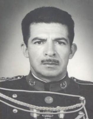 Gammelt svart-hvitt-foto av en ung og alvorlig Rios Montt i uniform.
