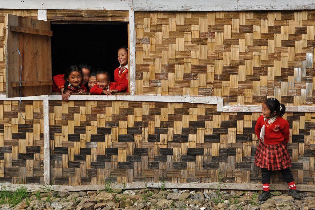 Smilende indiske skolejenter i røde uniformer titter ut av vinduet på skolen sin. Foto.