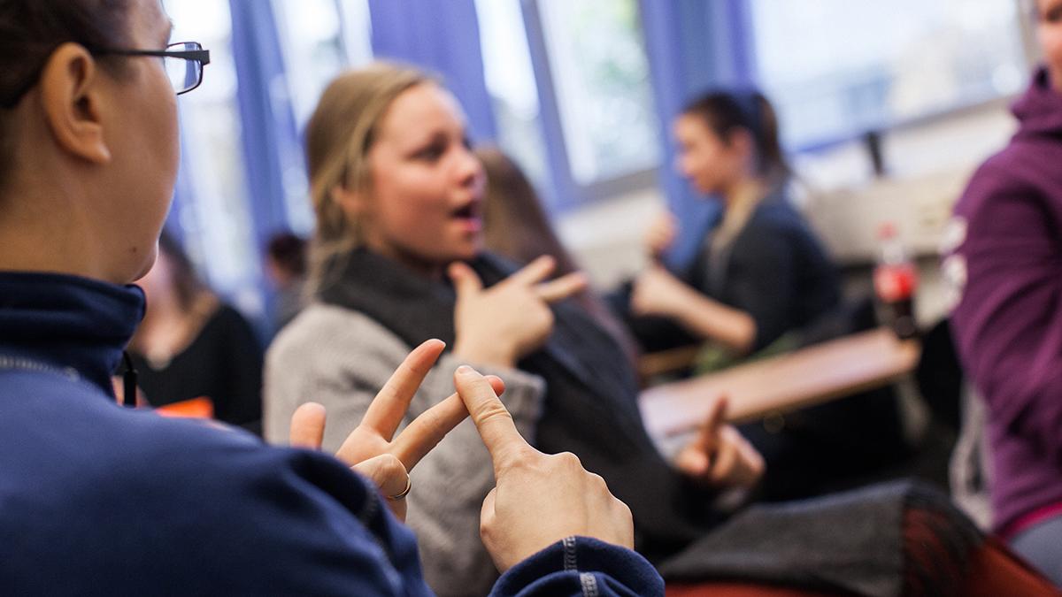 To studenter i forgrunnen som kommuniserer med tegnspråk. To andre mennesker i bakgrunnen.