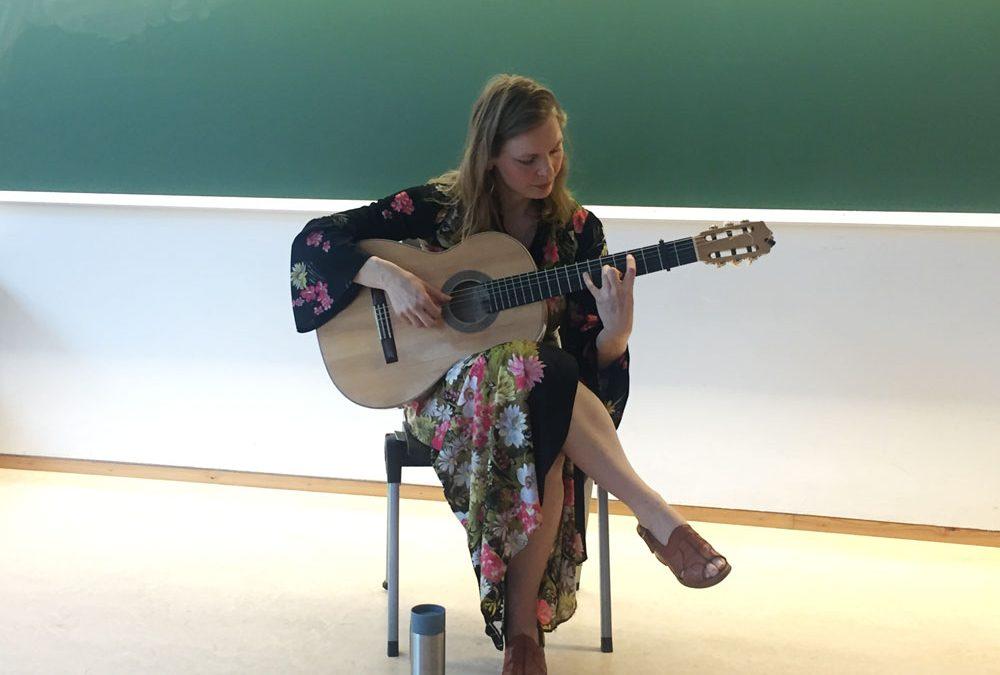 Flamencogitarist Bettina Flater sitter på en stol og spiller gitar