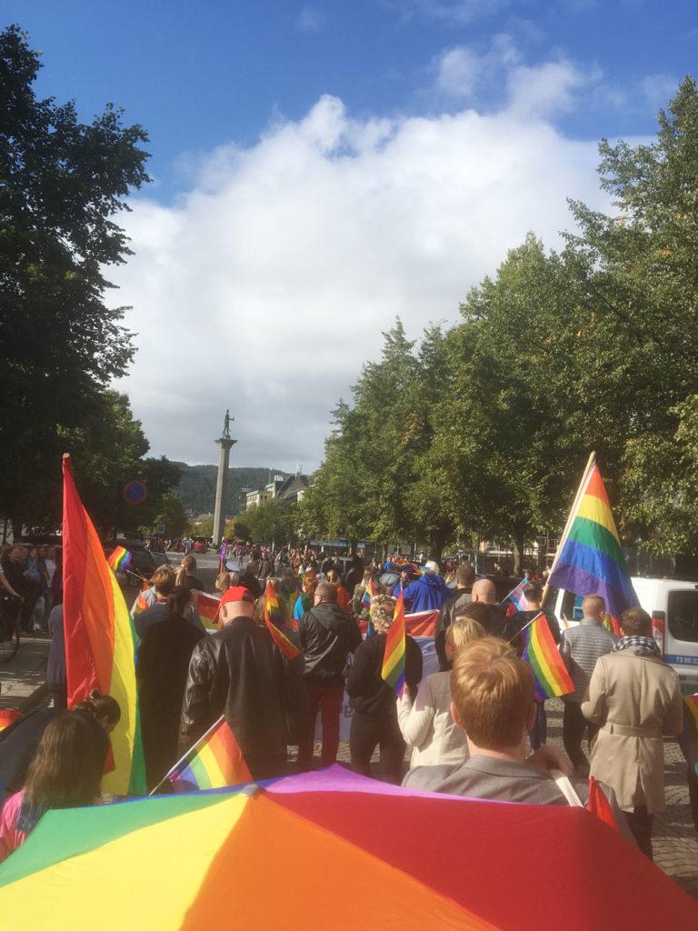 Folkemengde med regnbueflagg som går i Pride-parade i Trondheim