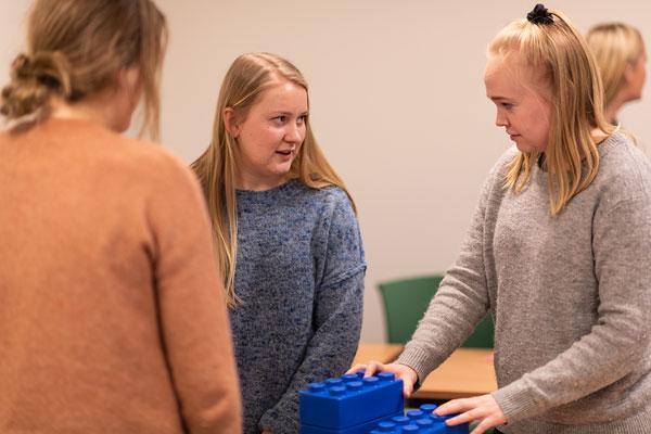 Studenter i gruppe som snakker sammen mens de jobber med store legoklosser. Foto
