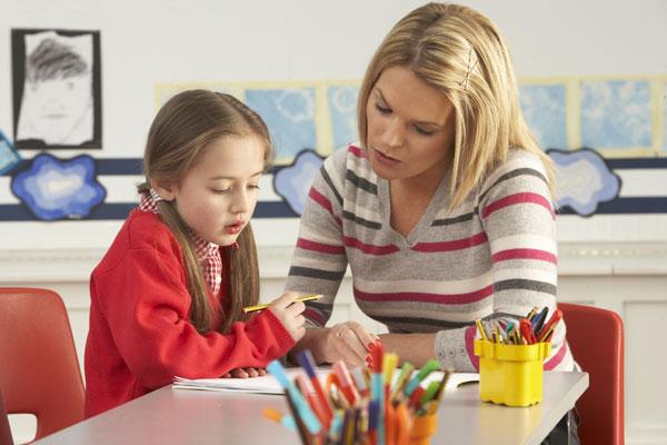Elev og lærer sitter sammen og jobber med en oppgave. foto