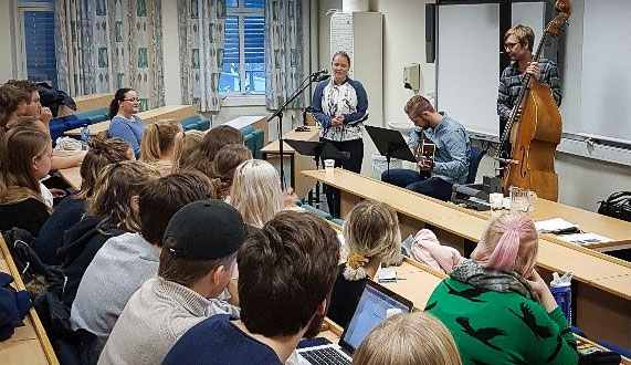 Studenter hører på musikere som spiller  på instrumenter. Foto