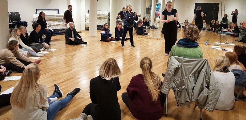 Studenter sitter i en ring på gulvet. To står oppreist og leser opp en tekst. Foto.
