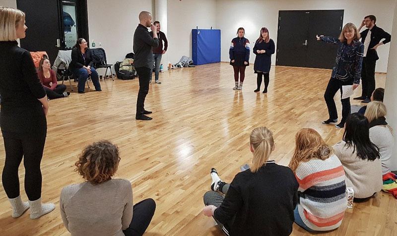 Foreleser forklarer noe til studenter som sitter i ring på gulvet. Foto