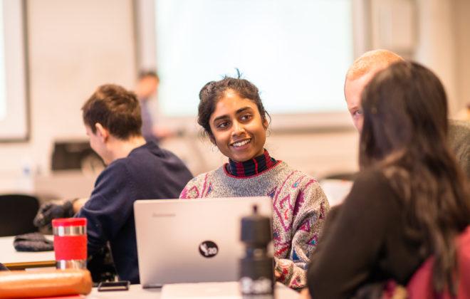 Student smiler til medstudenter i gruppearbeidet. foto