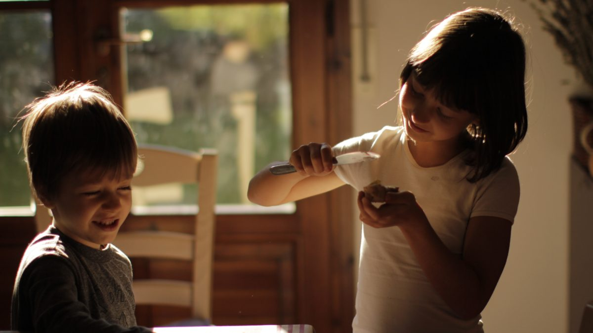 Gutt og jente som smører mat ved et kjøkkenbord i morgenlys. Foto.