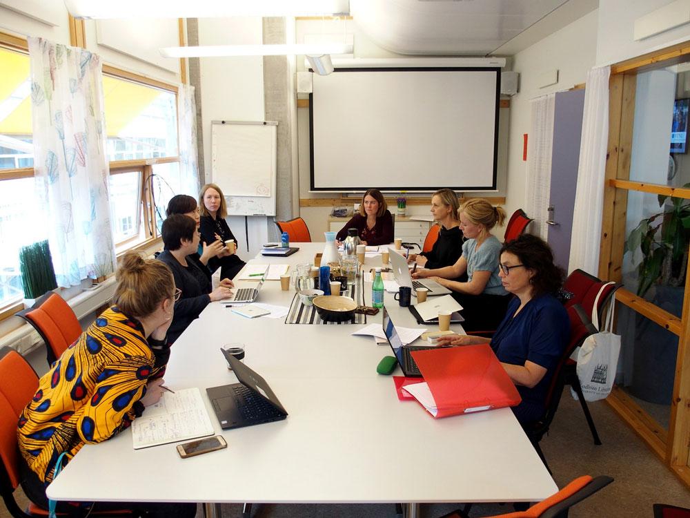 Forskere og studenter rundt møtebord