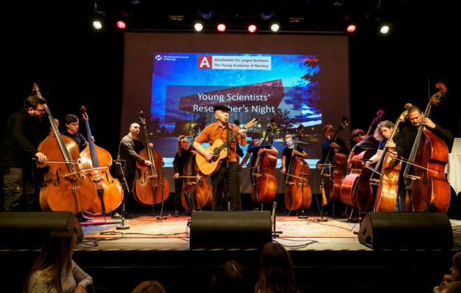 Ti kontrabassister og en gitarist på scenen
