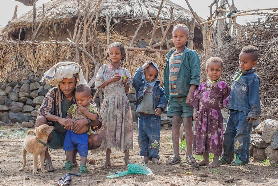 Fem barn og en voksen står utenfor en hytte. Foto.