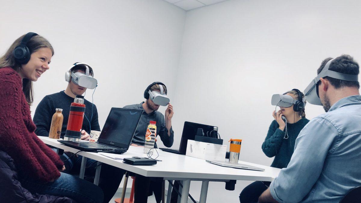 5 studenter sitter rundt et bord, fire av dem har på VR-briller. Foto.