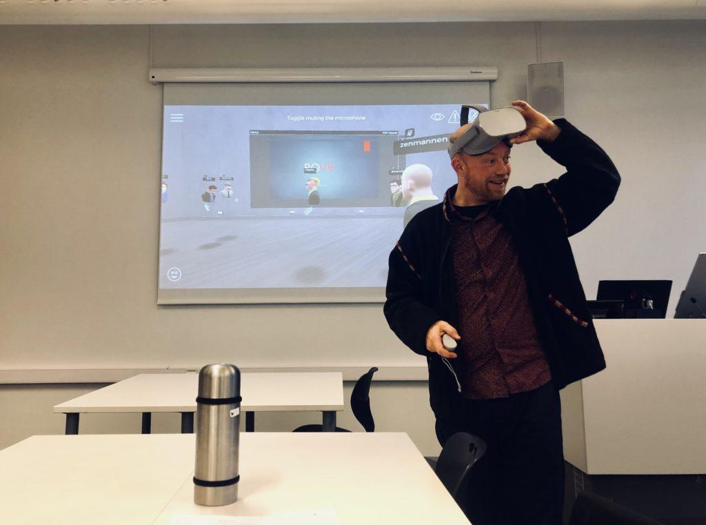 Håkon Fyhn står i undervisningsrommet. Han har på seg VR-briller. Foto.