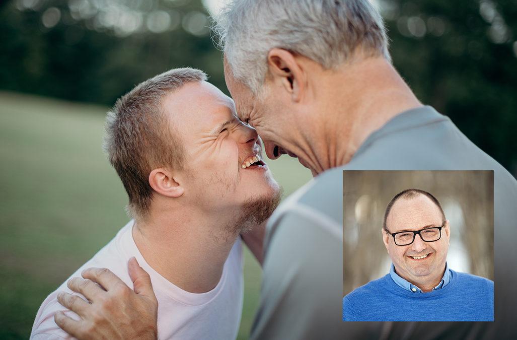 Mann med downs syndrom ser smilende en annen mann i øynene. Portrett av Odd Morten Mjøen er innfelt.