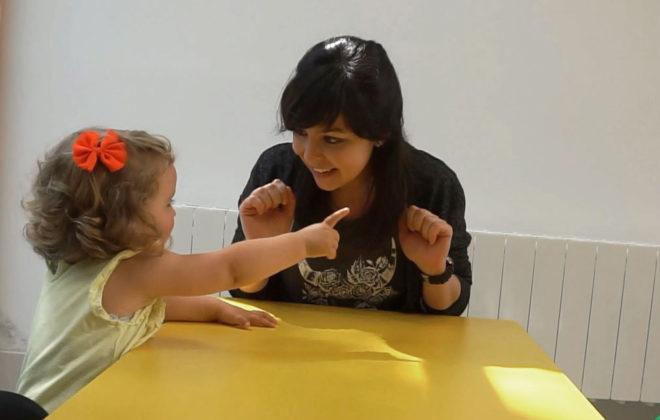 Barn og dame i samtale ved bord