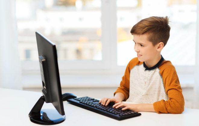 Gutt som sitter foran datamaskin