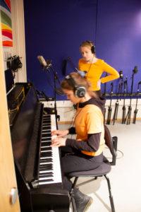 To jenter med headset i musikkstudio. En ved et piano en står ved siden av.
