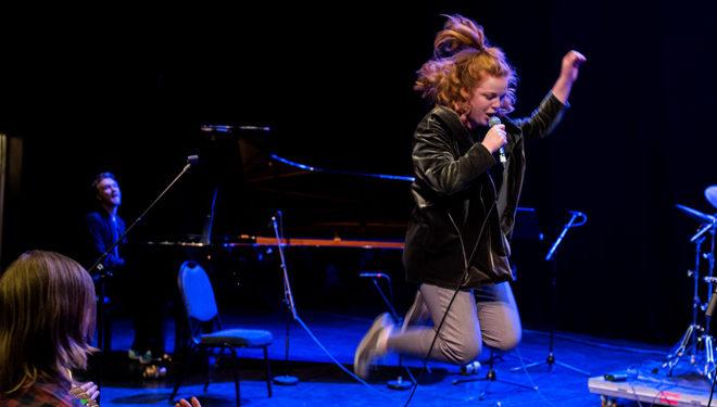 Kvinne som hopper og synger på en scene