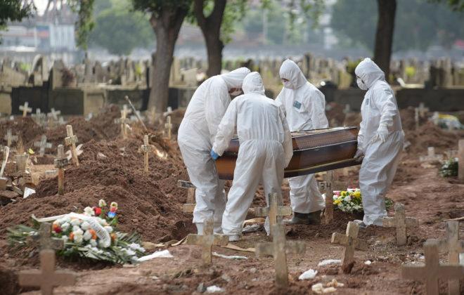 Fire personer iført fullt smittevernutstyr bærer en kiste på en gravlund i Rio, Brasil. Foto.
