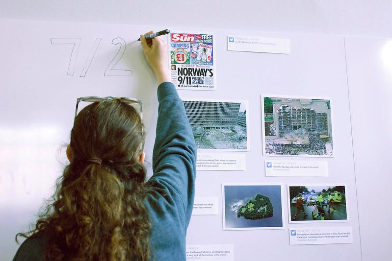 Dame skriver på en tavle der det henger utklipp med nyhetsbilder fra 22. juli. Foto