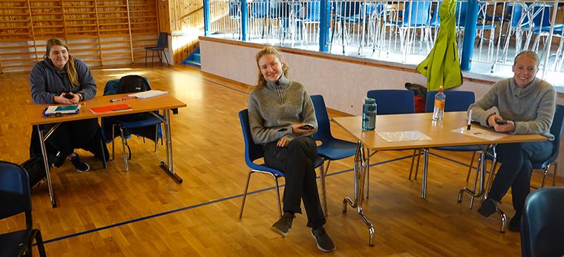 Tre masterstudenter sitter ved bord i gymsal ved Mausund Feltstasjon. foto