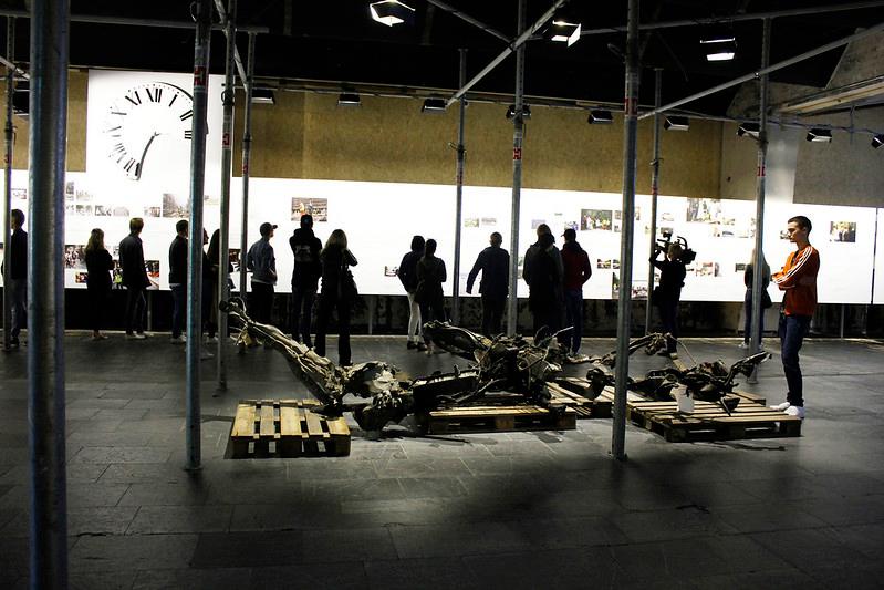 Utstilling i 22. julisenteret. Mann ser på restene fra bilen som ble sprengt.