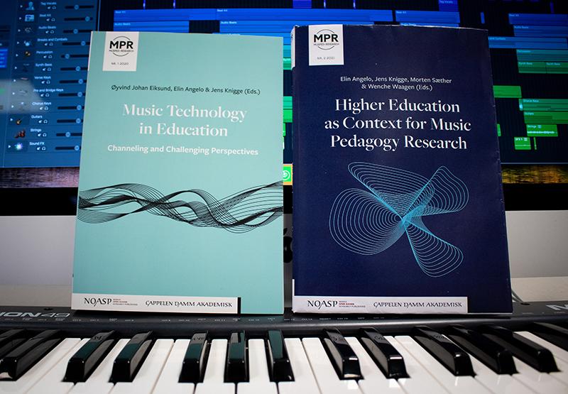 To bøker som står oppå tangenter, foran en datamaskin med musikkprogram. Foto