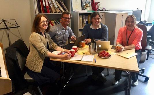 Fire personer sitter rundt et bord og har et møte. Foto