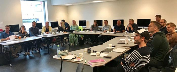16 mennesker som sitter i et klasserom. Foto
