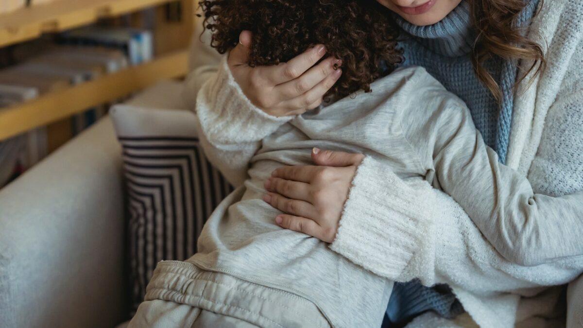 Kvinne trøster og klemmer et barn. Foto.
