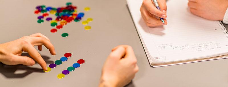 Hender som lager mønster med små fargede brikker. Hånd som holder penn. Foto