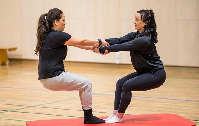 To studenter som gjør en øvelse sammen i gymsal. Foto