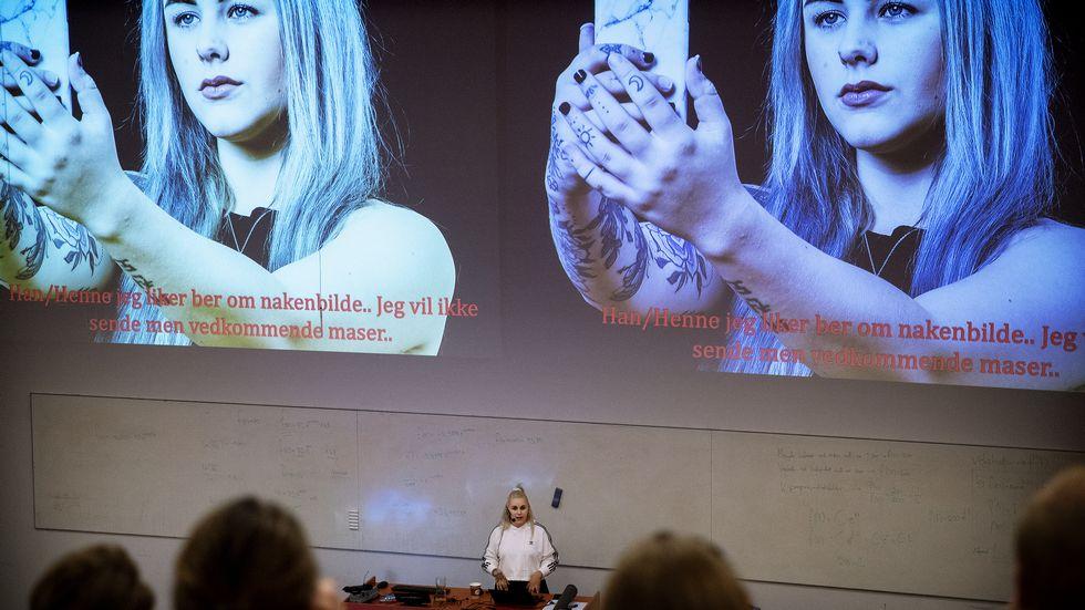 Bilde av en forelesning der en person holder foredrag, i bakgrunnen et bilde av Mia Landsem med telefon i hånda. Foto: Adresseavisen / Rune Petter Ness