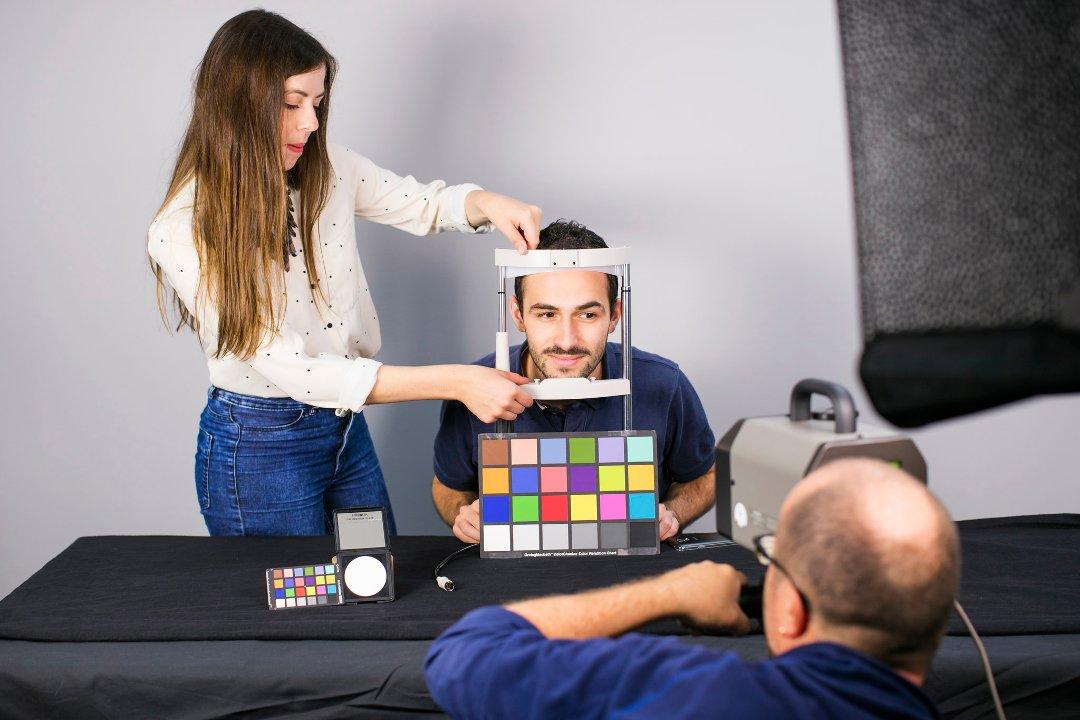 Jente som holder en bilderamme foran hodet på en ung mann.
