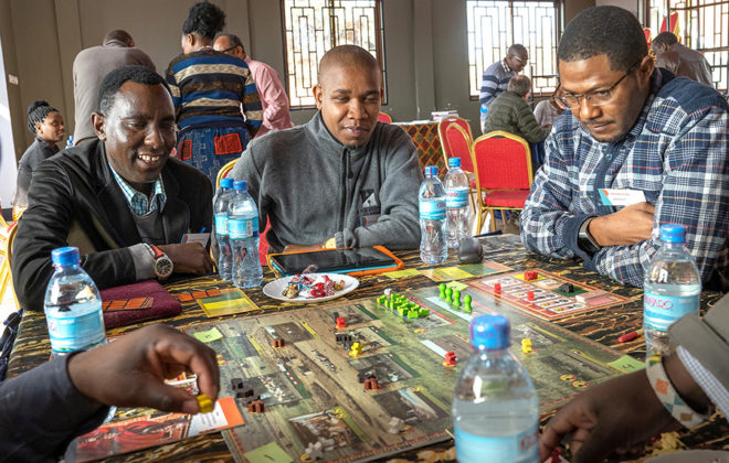 People in Tanzania playing the Savannah Life board game. Photo