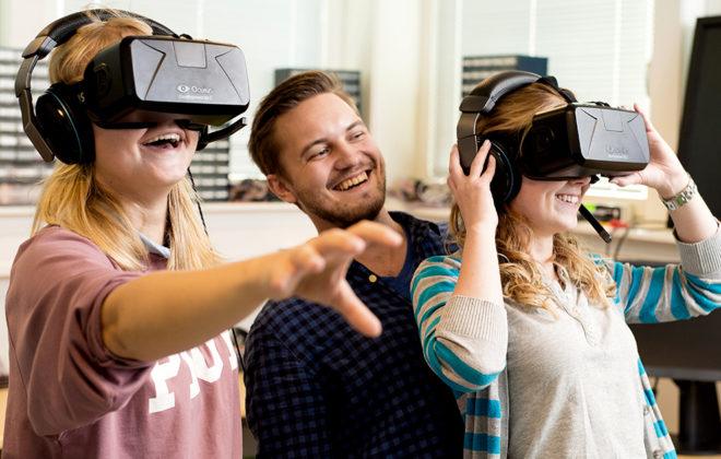 To studenter so ser gjennom VR-briller sammen med veileder. Foto