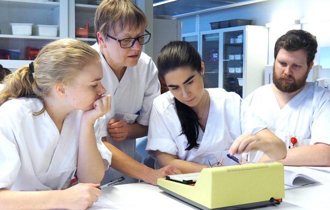 Tre bioingeniør-studenter på lab med lærer. Foto