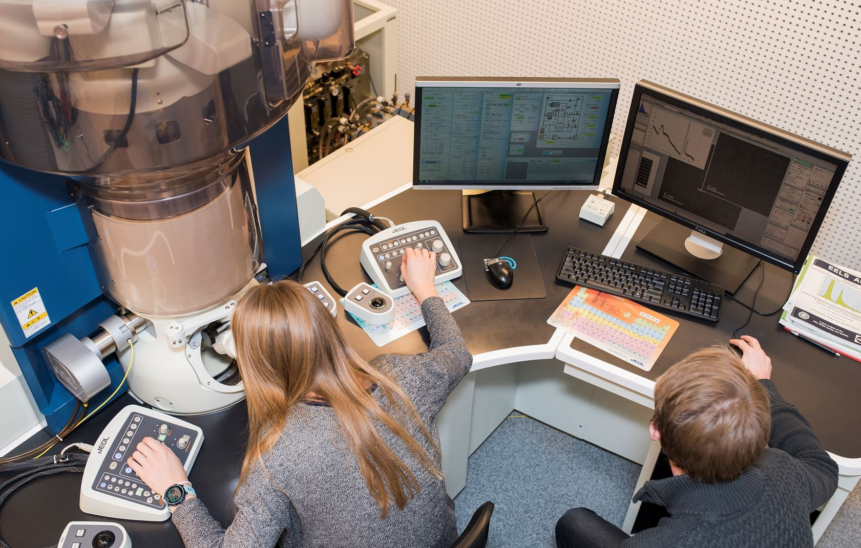Two researchers working in the TEM lab. Photo taken from above. Photo