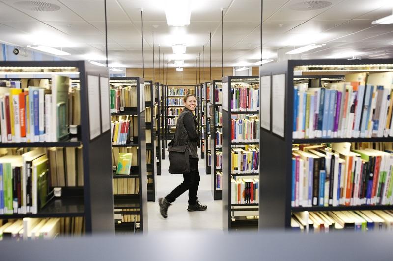Kvinne blant bokhyller i biblioteket