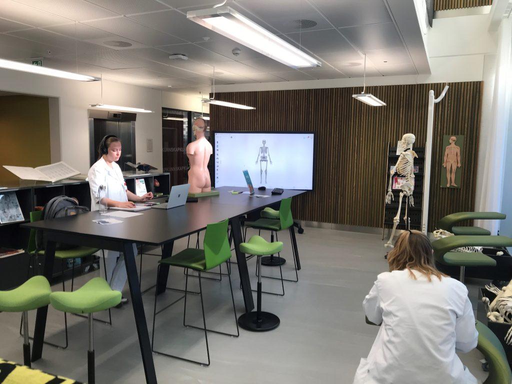 Oversiktsbilde av to studenter som jobber i KUBA med bord, skjeletter og storskjerm
