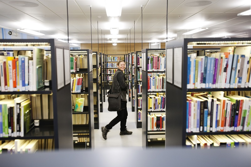 Woman walking along book shelves in the library