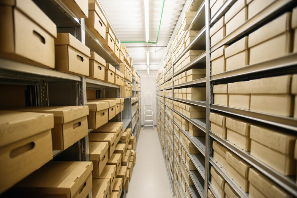 Archival boxes with photographs on shelves in an archive
