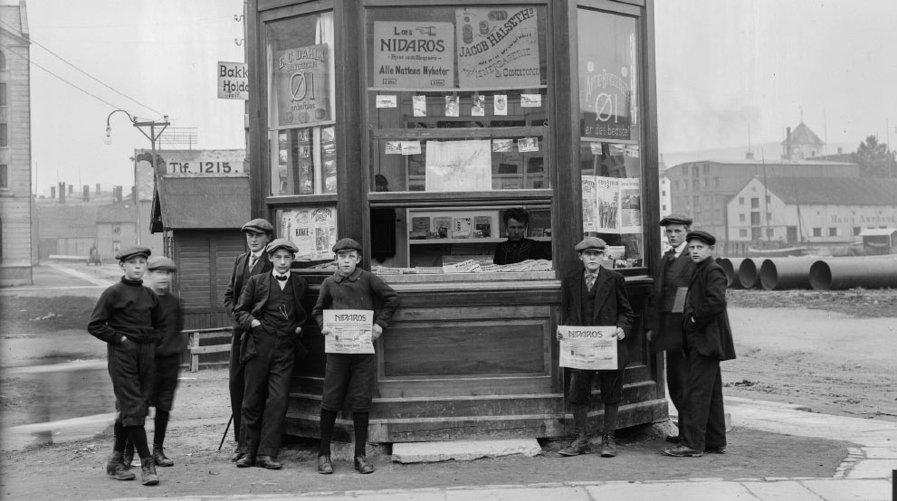 Newspaper stand with boys standing outside holding newspapers