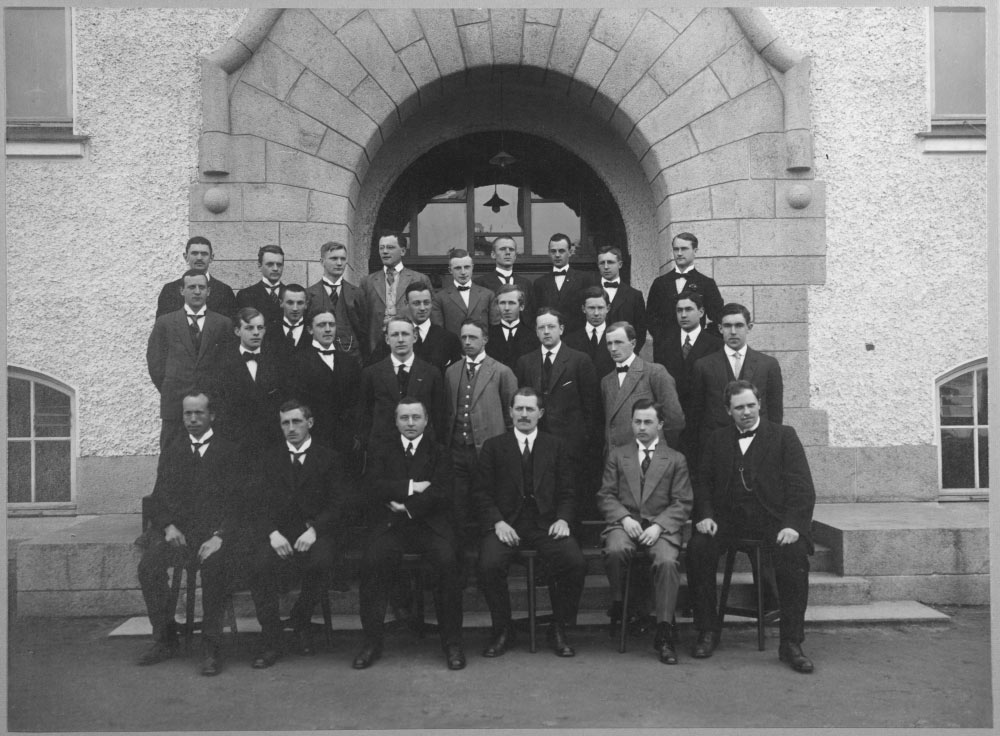Men in suits posing outside a concrete building